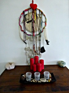 Candle setting with red candles and  Ancestral Medicine Shield